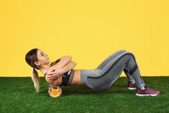 Photo amazing fit young woman do exercise with foam roller on green grass over yellow background. Photo amazing fit young woman do exercise with foam roller on stock photos