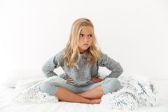 Photo of angry little girl with hands on her waist sitting with Stock Photo