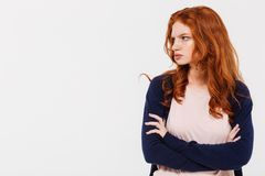 Angry pretty young redhead lady with arms crossed Stock Photo