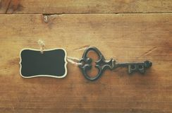 photo of antique key and empty blackboard tag over old wooden table. royalty free stock photos