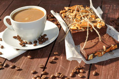 A photo of an an appetizing chocolate cake decorated with small pieces of biscuits and placed wrapped in a rustic paper and a cup Stock Image