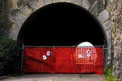 Restricted area, stop sign. Photo of an arched tunnel through massive rock or mountain. Some asphalt road is closed. You may see some fences and various stop Stock Photography