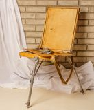 Photo of Artist tool box. Painter`s case with portable easel. Th. E sketchbook with palette, paints and brushes on brick background royalty free stock photos