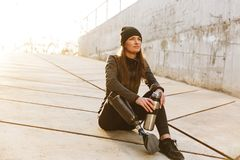Photo of athletic disabled girl with prosthetic leg in sportswear, sitting on concrete floor outdoors and looking aside. Photo of athletic disabled girl with stock photography