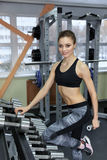 Photo of athletic young girl doing a fitness workout with dumbbells in the gym royalty free stock photos