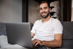 Photo of attractive bachelor using silver laptop while sitting on couch in living room. Photo of attractive bachelor 30s wearing casual t-shirt using silver royalty free stock photos