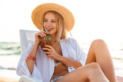 Photo of attractive blonde woman 20s in straw hat drinking exoti. C cocktail while sitting in deck chair at sea coast during summer sunrise Stock Photo
