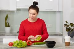 Photo of attractive future mother, holds lettuce, prepares vegetable salad for breakfast, dressed in casual red clothes, cooks at stock photos