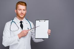 Photo of attractive handsome good-looking doc isolated on dark g. Ray background with copy space for text point on empty place in document stand in white wear royalty free stock photography
