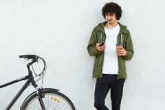 Photo of attractive man wears fashionable green anorak and black jeans, has little beard, holds cell phone in one hand and paper c. Up of coffee in other, reads stock photos