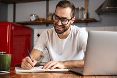 Photo of attractive man writing down notes while using silver laptop on kitchen table. Photo of attractive man 30s wearing eyeglasses writing down notes while royalty free stock images