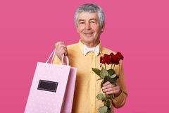 Photo of attractive mature man with pleasant facial expression, dressed in yellow shirt with white bowtie, carries pink bag with stock photo