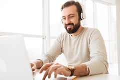Photo of attractive mature man 30s in casual clothing typing tex. T message or working on laptop while listening to music via earphones Royalty Free Stock Photo
