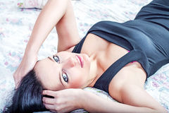 Photo of attractive sexy brunette woman lying on bed in hotel ro Stock Images