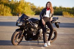 Photo of attractive woman has real adventure outdoor, stands near motorbike, dressed in bikers outfit, enjoys sunny day and calm a stock photography