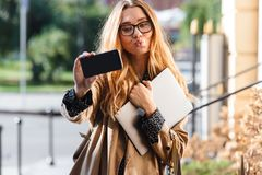 Photo of attractive woman 20s holding laptop and using smartphone in city street. Photo of attractive woman 20s holding laptop and using smartphone while walking royalty free stock photos