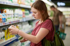 Photo of attractive young female consumer model with bobbed hairstyle, dressed in casual t shirt, stands in big store, holds bottl. E of milk, focused on label stock photos