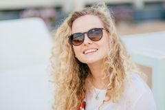 Photo of attractive young female has light curly hair, wears trendy shades, has toothy smile, shows white teeth, recreats outdoor,. Smiles as recieves stock photos