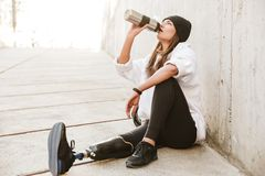 Photo of attractive young handicapped woman having bionic leg in. Streetwear, sitting on concrete floor outdoor and drinking water from metal cup royalty free stock image
