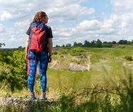 Photo from back of female tourist with backpack on hill ,blue sky background. Summer day stock images