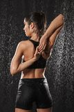 Photo from back of gorgeous slim woman in sports clothing standing under the rain drops after workout, isolated over black royalty free stock photo