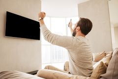 Photo from back of happy mature man clenching fists and rejoicin. G while watching on copyspace screen of television in living room Stock Image