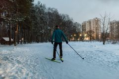 Photo from back of male skier in blue jacket in winter park. On background of houses Stock Photo