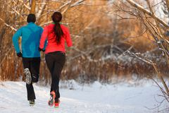 Photo from back of sports woman and man running on winter stock images