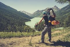 Photo from back of tourist man with walking sticks with his hands up on mountain hill near lake. tourist holding sticks for Nordic stock photography