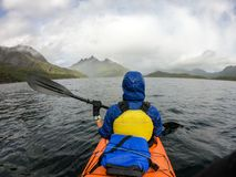 Photo from back of tourist with paddle on canoe floating. On river royalty free stock images