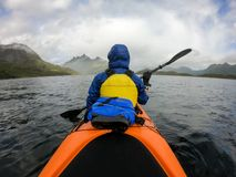Photo from back of tourist with paddle on canoe floating. On river stock photography