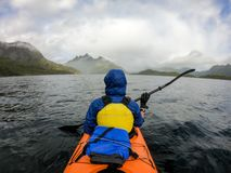 Photo from back of tourist with paddle on canoe floating. On river stock image