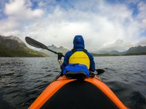 Photo from back of tourist with paddle on canoe floating. On river stock images