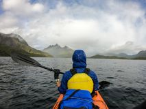 Photo from back of tourist with paddle on canoe floating. On river stock photos