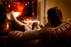 Photo from back of woman warming up fireplace at Christmas Royalty Free Stock Photo