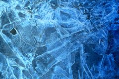 Photo background frozen ice. Photo background bright blue frosted thin ice with cracks in the spring Royalty Free Stock Image