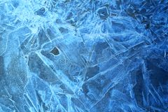Photo background frozen ice. Photo background bright blue frosted thin ice with cracks in the spring Stock Photos
