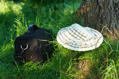 Photo bag and hat are on the green grass Royalty Free Stock Photos