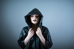 Photo of a bald woman in a raincoat with the hoods on. Emotive photo of a beautiful bald woman in a black raincoat with the hoods on royalty free stock photography