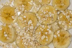 Banana slices with oats and honey close up royalty free stock images