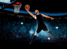 Photo of basketball player makes layup in the game. NBA. Basketball game. Sportsman plays basketball Royalty Free Stock Image