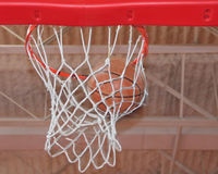 Photo of basketball swishing through a hoop. Basketball going through hoop after thrown royalty free stock photography