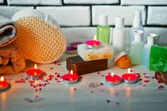 Photo of bathrooms, spa treatments. Transparent bottles, loofah, pieces of soap, bath salts, candles. Comfort royalty free stock image