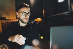 Photo bearded banker relaxing modern loft office after work day. Man sitting in vintage chair at night. Using. Photo bearded banker relaxing on modern loft royalty free stock image