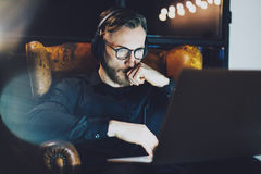 Photo bearded businessman wearing glasses relaxing modern loft office.Man sitting in vintage chair,listening music Royalty Free Stock Image