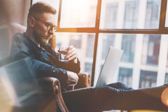 Photo bearded businessman working on modern loft office. Man sitting in vintage chair, holding glass water. Using. Bearded young businessman working on modern Stock Image