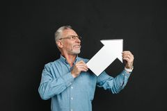 Photo of bearded gentleman 60s with grey hair wearing eyeglasses. Holding blank speech arrow pointer directing aside isolated over black background Stock Photo