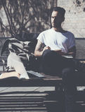Photo bearded man wearing white tshirt sitting city park and draws notepad. Studying at the University, working project Royalty Free Stock Photo