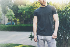 Photo Bearded Muscular Man Wearing Black Blank t-shirt in summer time. Green City Garden.Relaxing time after hard work. Day. Blurred Background.Front view Stock Photo