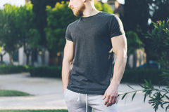 Photo Bearded Muscular Man Wearing Black Empty t-shirt and shorts in summer holiday. Green City Garden Park Background. Front view. Horizontal Mockup Royalty Free Stock Photography